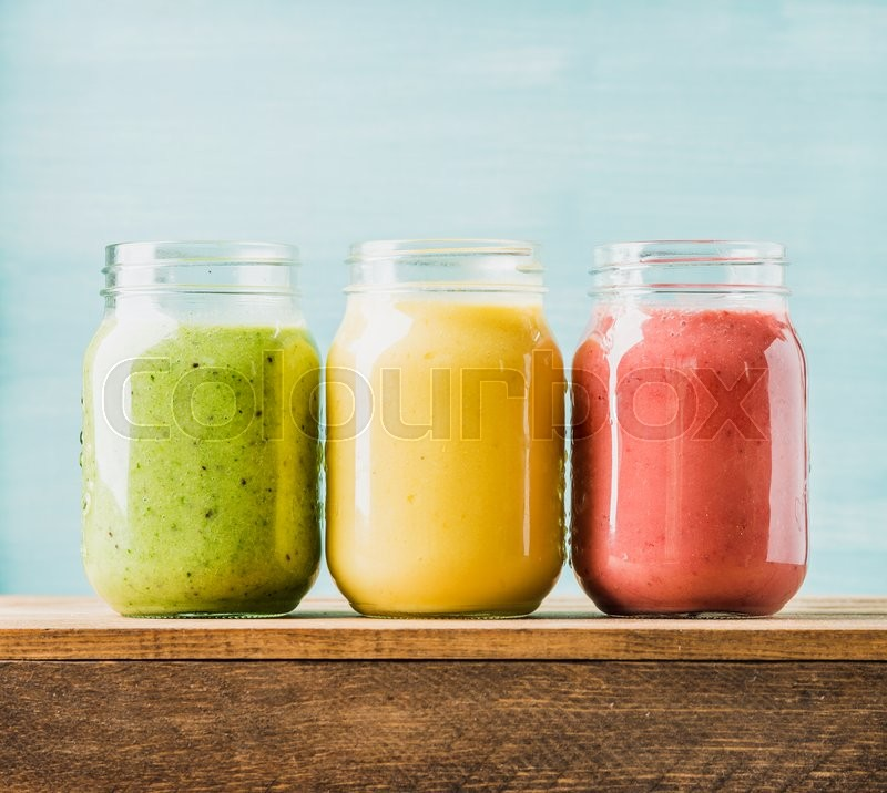 Stock image of 'Freshly blended fruit smoothies of various colors and tastes in glass jars. Yellow, red, green. Turquoise blue background'