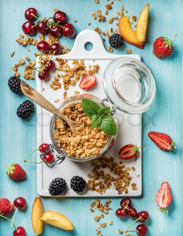 Stock image of 'Healthy breakfast ingredients. Oat granola in open glass jar, fruit, berries and mint on blue background with white ceramic board in center, top view'