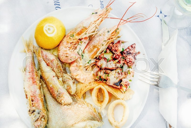 Stock image of 'Cooked seafood on plate with lemon and wine. Prawns, squid, octopus, mullet fish and seabream. Traditional Mediterranean dish on Greek island of Kastelorizo'