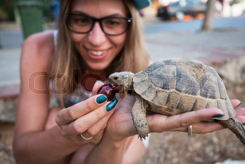 Stock image of 'Happy young woman feeding turtle with cherry'