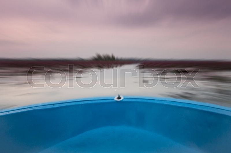 Stock image of 'Small boat in the lake of red lotus with blur background, stock photo'
