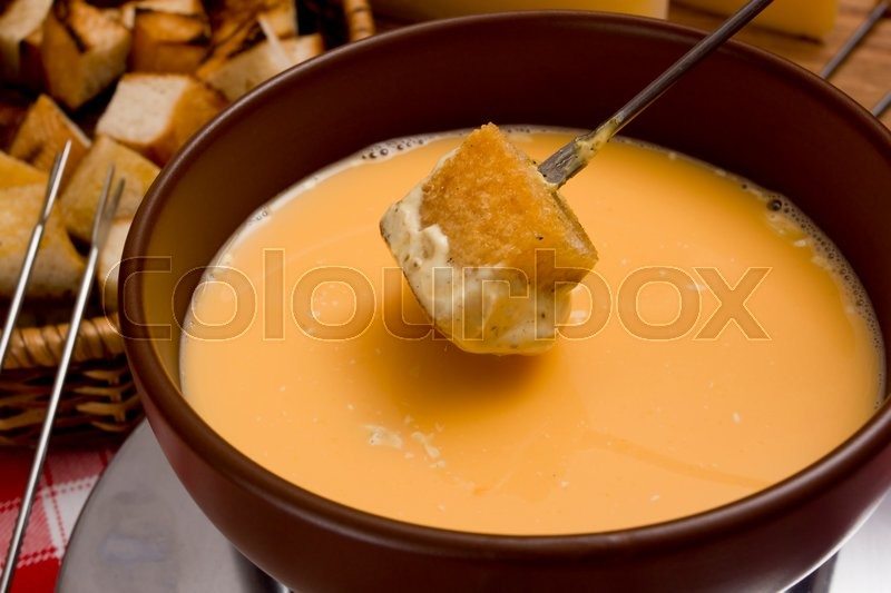 Stock image of 'Сheese fondue – piece of bread (croutons) in a liquid cheese'