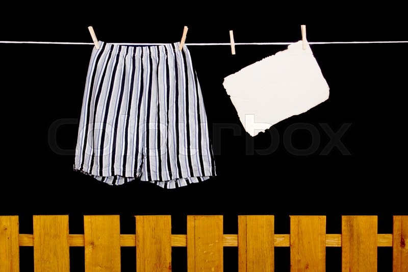 Stock image of 'Men's underwear hanging on a clothesline over the fence'