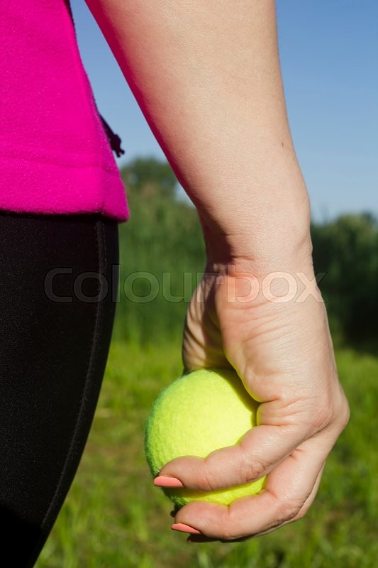 Stock image of 'Athlete woman holding a yellow tennis ball'
