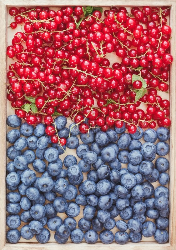 Stock image of 'Assorted berries. Fresh redcurrants and blueberries on wooden tray, top view'