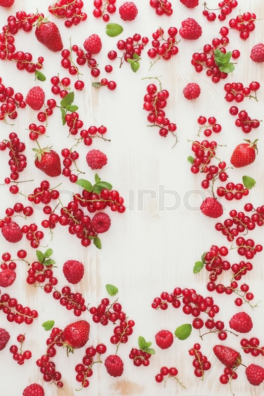 Stock image of 'Fresh berry fruits. Fresh organic berry fruit scattered on rustic table with space for text in the middle. Overhead view, blank space'