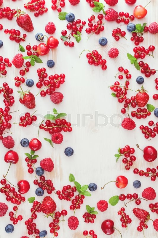 Stock image of 'Summer fruit background. Fresh organic berry fruit scattered on rustic table with space for text in the middle. Overhead view, blank space'