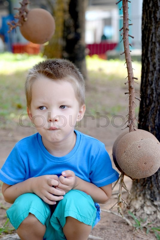 Stock image of 'child resting near coconut tree in a tropical garden'
