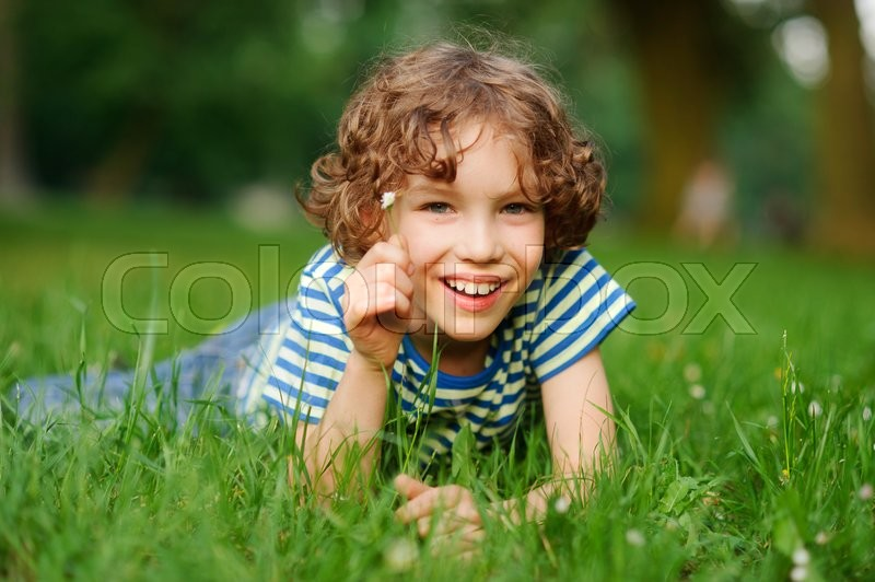 Stock image of 'The boy of 8-9 years lies in a dense green grass. The boy has curly hair, a turned-up nose, chubby lips and blue eyes.He has in a hand a small floret. The boy looks in a camera and smiles.'