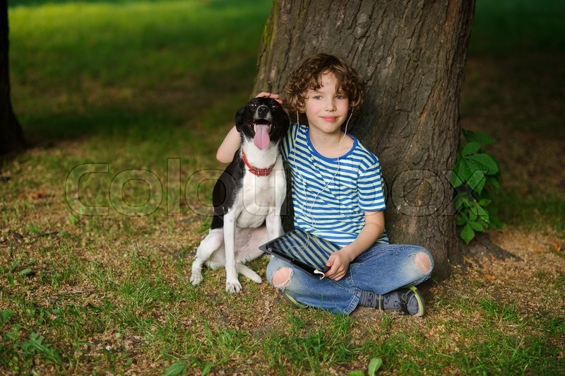 Stock image of 'The boy with a dog sits on the earth under a tree. The child sits having crossed legs. He has put a hand on the head of a pet. On a lap the boy has a tablet. On a face a thoughtful smile.'
