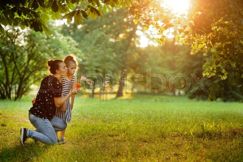 Stock image of 'Mother with the daughter start up soap bubbles. On a deserted lawn in park mother plays with the daughter. They spend together time in the fresh air.'