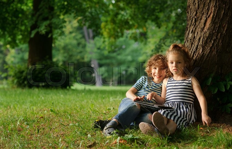 Stock image of 'The boy and the girl of 7-8 years sit under a big tree in park.Children sit on the earth having extended legs.They hold the small laptop.On a background green park.Children look in a camera.'