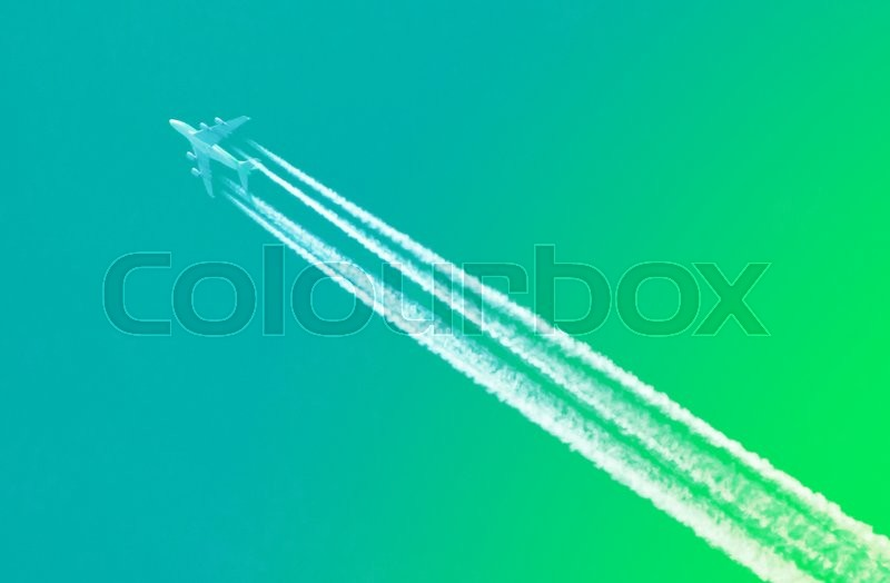 Stock image of 'Large aircraft flying in sky, 4 stripes in the sky - Bright green sky'