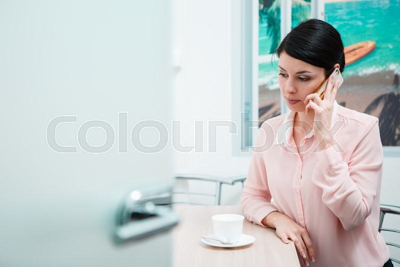 Stock image of 'Young woman in the office talking on phone in kitchen room'