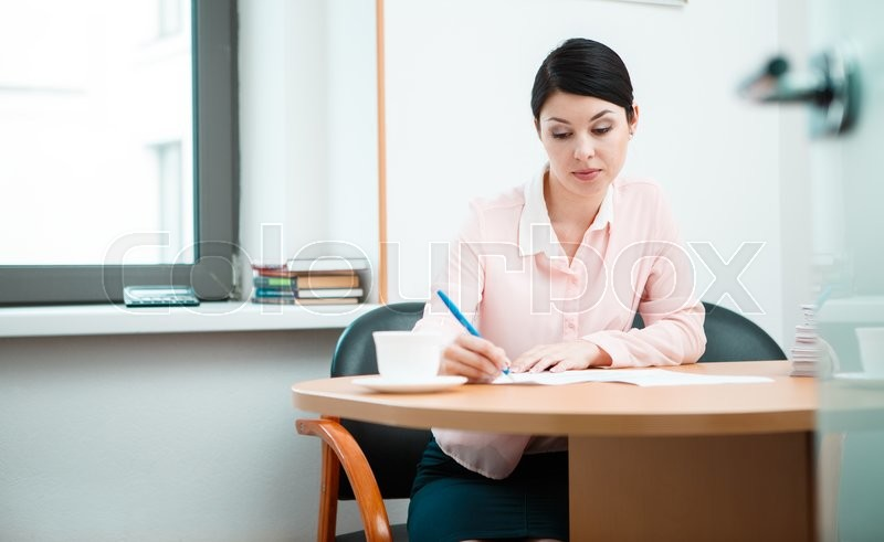 Stock image of 'Woman Writing in paper. '