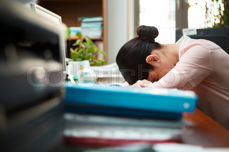 Stock image of 'Tired businesswoman sleeping on the desk.'