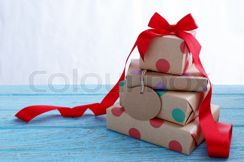 Stock image of 'Presents for birthday with red ribbon on blue wooden table'