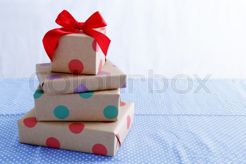 Stock image of 'Presents for birthday with red bow on table with space'