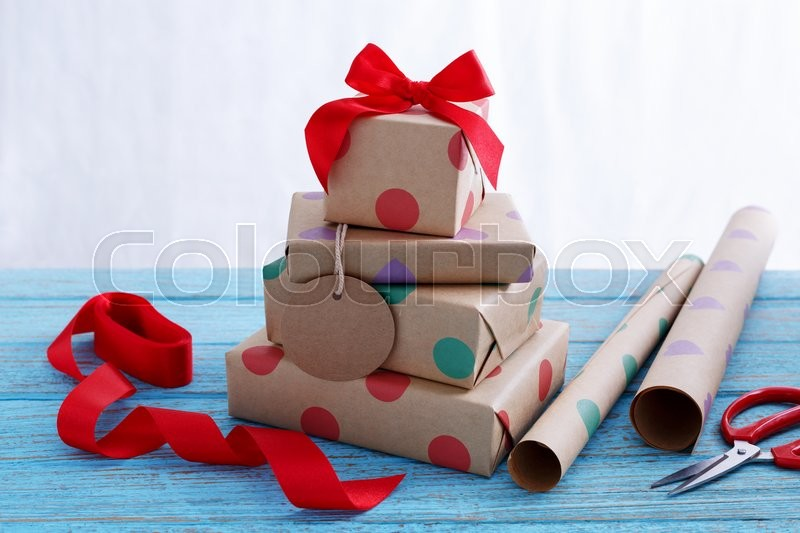 Stock image of 'Presents for birthday with wrapping paper and red ribbon on wood table'