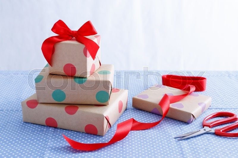 Stock image of 'Presents for birthday with wrapped boxes and red ribbon on table'