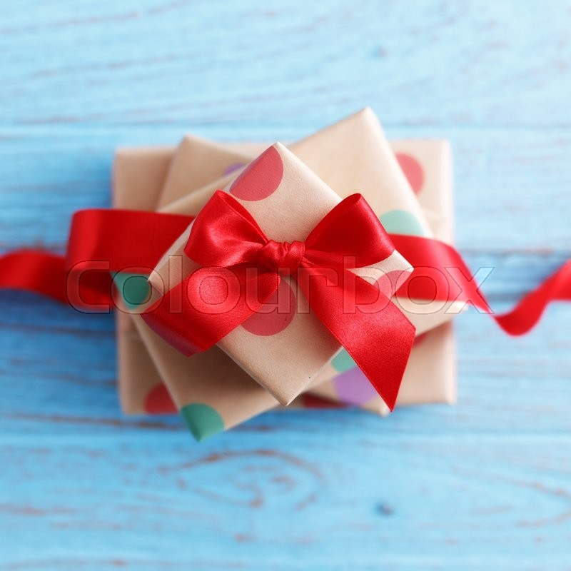 Stock image of 'Presents for birthday with red bow and ribbon on wood table'