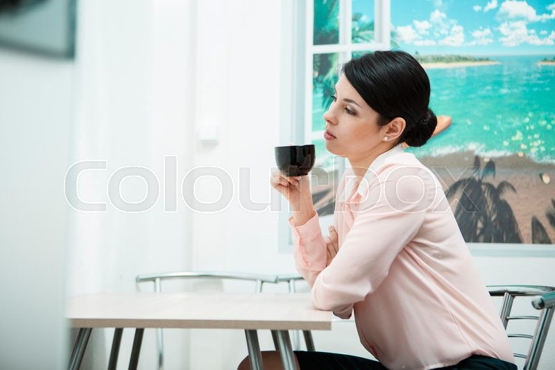 Stock image of 'Coffee break. Woman resting with cup of in office kitchen.'