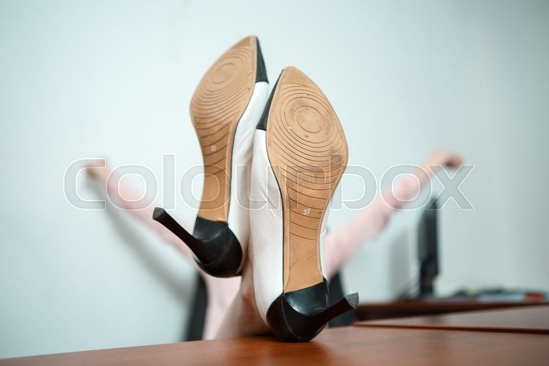 Stock image of 'Relaxed business woman sitting in a chair with legs over the table. Focused on shoes.'