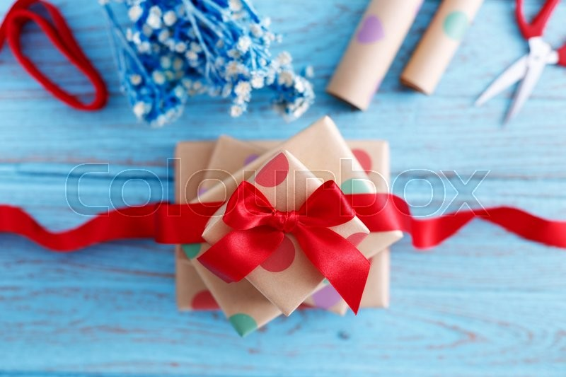 Stock image of 'Presents for birthday with wrapping paper and red bow on blue wood table'