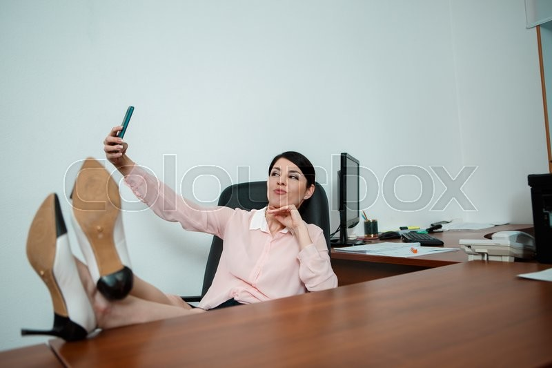 Stock image of 'Relaxed business woman sitting in a chair with legs over the table a taking selfie.'