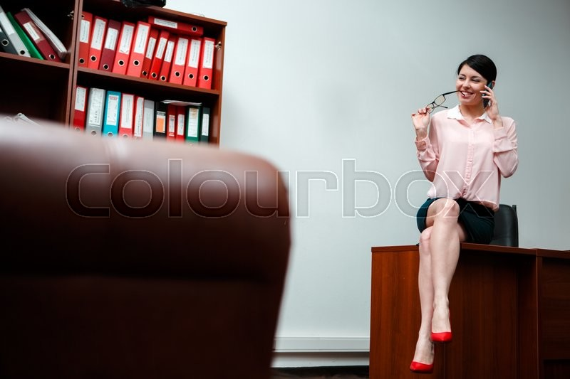 Stock image of 'Businesswoman talking on the phone in office sitting on table.'