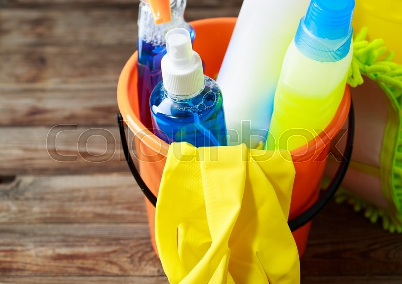 Stock image of 'Plastic bucket with cleaning supplies on wood background'
