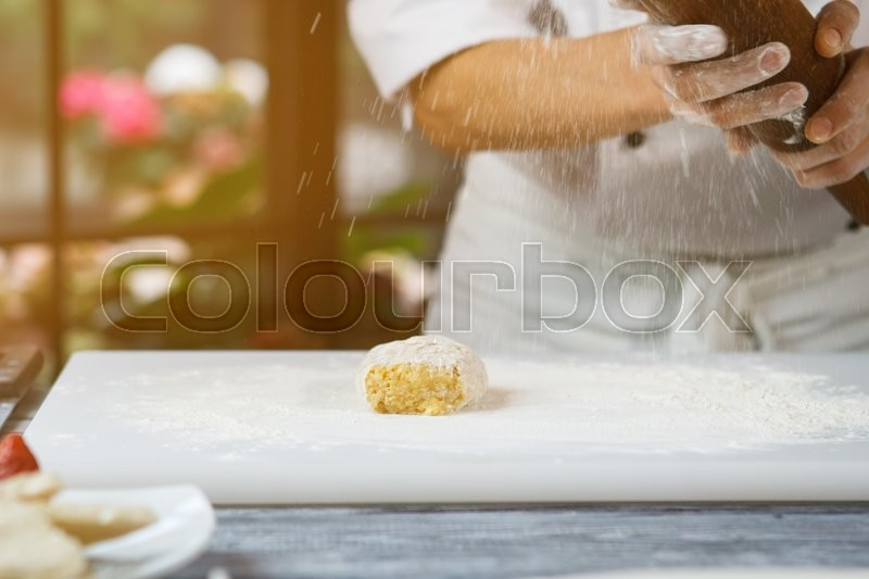 Stock image of 'Flour falling onto dough. Man's hands with rolling pin. Flour of high quality. Confectioner's busy morning.'