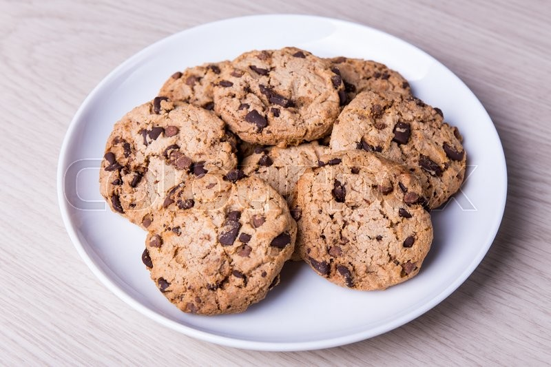 Stock image of 'close up of chocolate chip cookies on white plate on wooden table background'