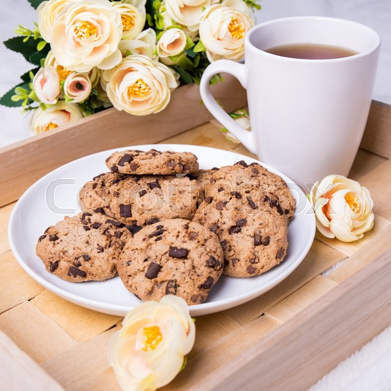 Stock image of 'close up of wooden tray with chocolate chip cookies, cup of tea and flowers'
