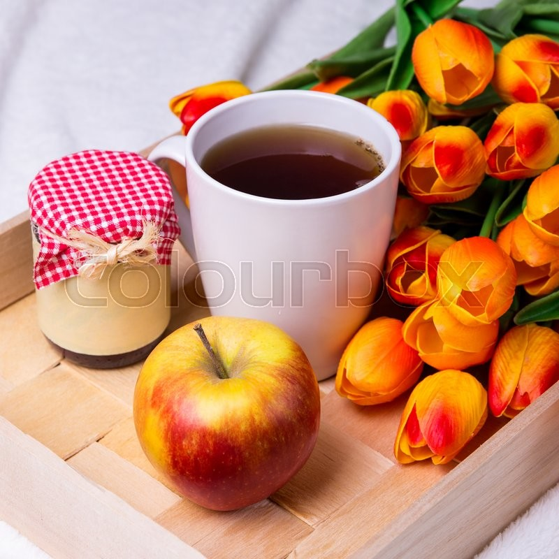 Stock image of 'close up of wooden tray with cup of tea, jar of jam or honey, apple and flowers'