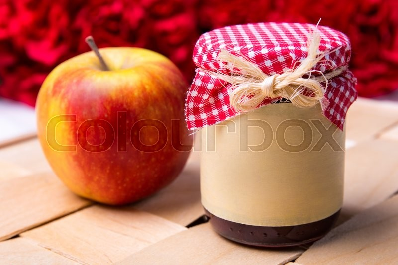 Stock image of 'close up of glass jar of jam or honey and red apple'