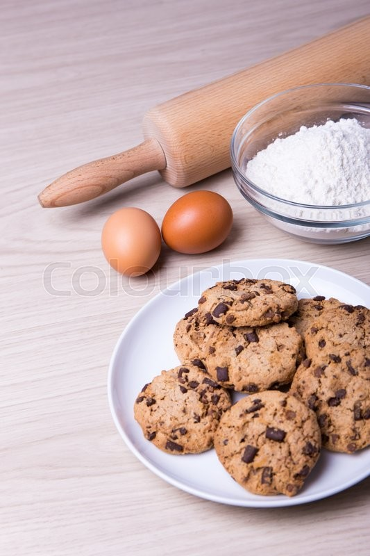 Stock image of 'bakery concept - chocolate chip cookies, eggs and flour on wooden table background'