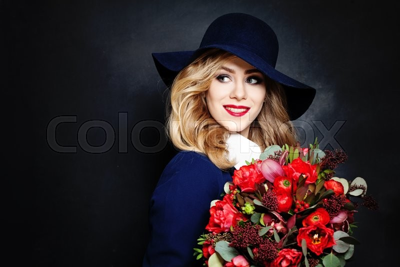 Stock image of 'Happy Lady Fashion Model with Flowers on Background with Copy Space for Text'