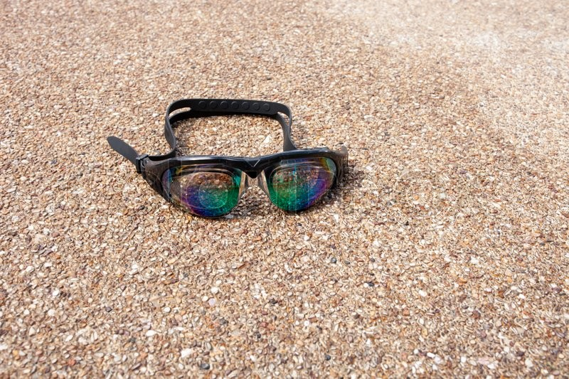 Stock image of 'Glasses for swimming on a cement floor with small stone near swimming pool.'