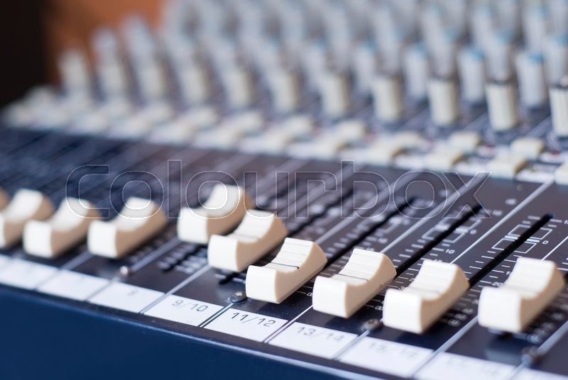 Stock image of 'Many knobs controllers and switches on a audio mixer'