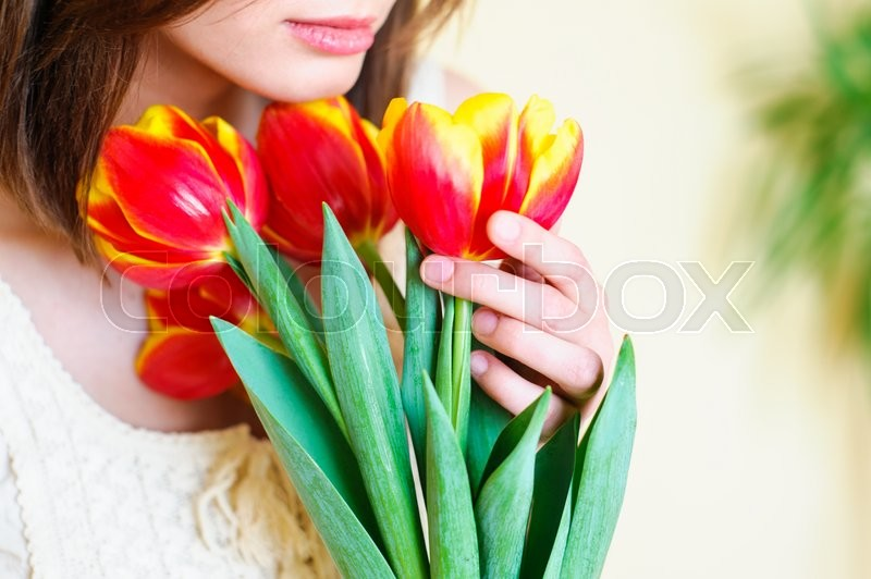 Stock image of 'Delicate nude girl holding tulips over her breasts '