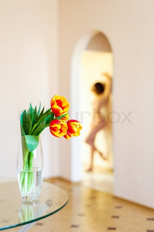 Stock image of 'Delicate nude girl posing on the background of tulips'