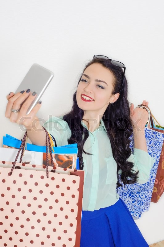 Stock image of 'Young beautiful smiling girl doing selfie while shopping'