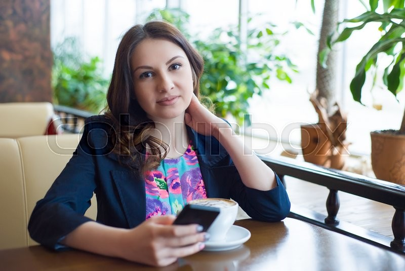 Stock image of 'a beautiful young girl drinking coffee in a cafe '