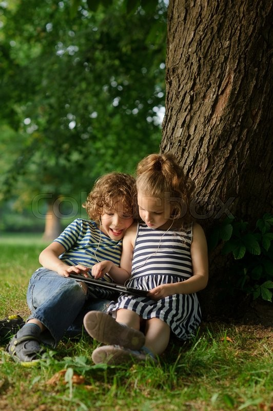 Stock image of 'The boy and the girl of 7-8 years sit on the earth under a tree and play on the tablet. They sit having leaned against a trunk of a big tree. On a lap tablet. In ears one earphones for two.'