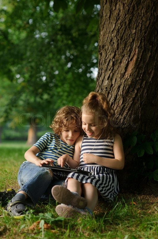 Stock image of 'Two children sit in park under a big tree and play on the tablet. . They sit having leaned against a trunk of a big tree. On a lap tablet. In ears one earphones for two.'