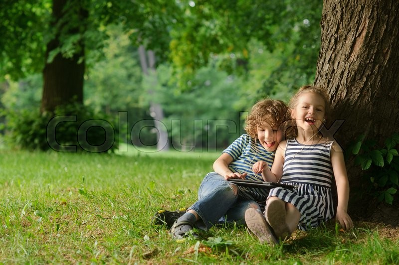 Stock image of 'The boy and the girl of 7-8 years sit under a tree having nestled and play on the tablet. Children are very keen. Them that - that has made laugh. Children laugh.'