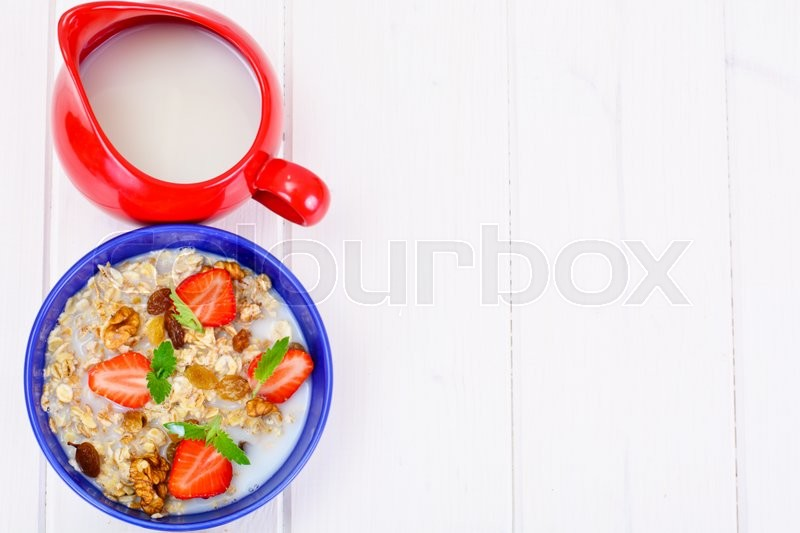 Stock image of 'Oatmeal with Raisins, Walnuts and Strawberries Studio Photo'