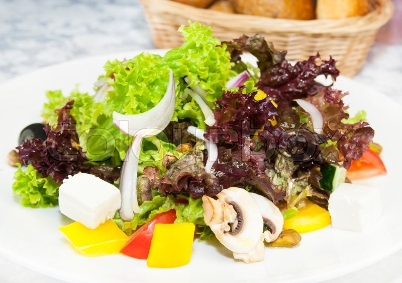 Stock image of 'Greek salad on a white background in the restaurant'