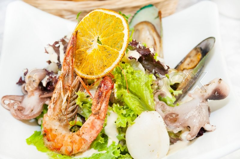 Stock image of 'Salad with vegetables and seafood on the table in a restaurant'